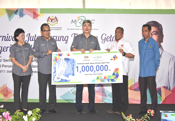 YB. Minister Dato' Seri Mah Siew Keong (centre) presenting a mock cheque for 1 million gloves to YBhg. Dato' Dr Hassan Merican (second from right), Director of Perak State Health Department.